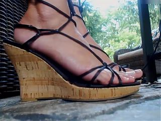 MILF shows her pretty feet in thin strappy wedge sandals.