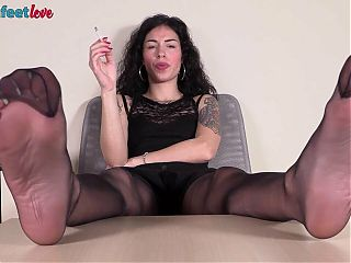 Teen somkes a cigarette with her nylon feet up in your face