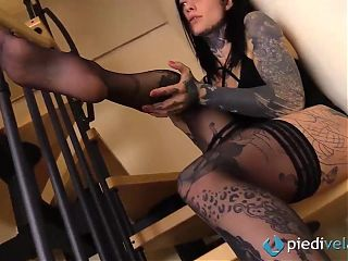 Tattoed girl takes off her stockings